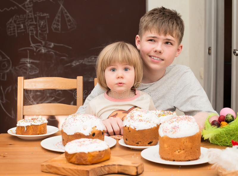 Children with traditional Easter homemade cakes and colored eggs. Teen boy and little girl sitting at the table full of royalty free stock photo