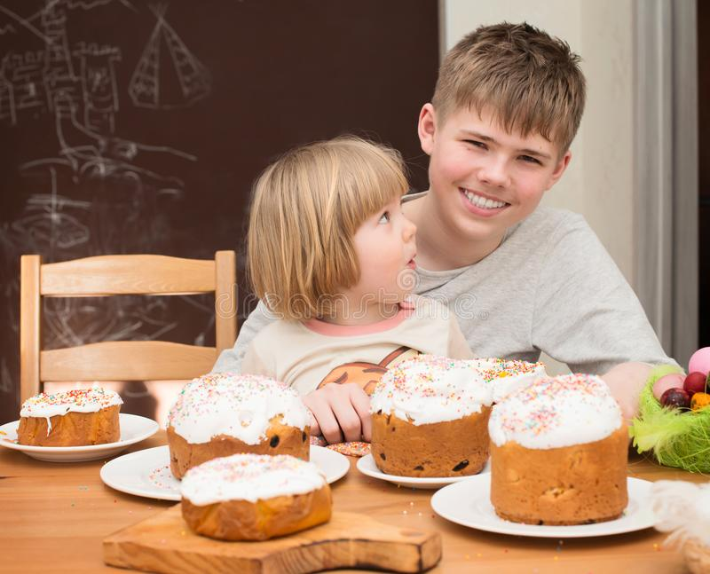 Children with traditional Easter homemade cakes and colored eggs. Teen boy and little girl sitting at the table full of royalty free stock image