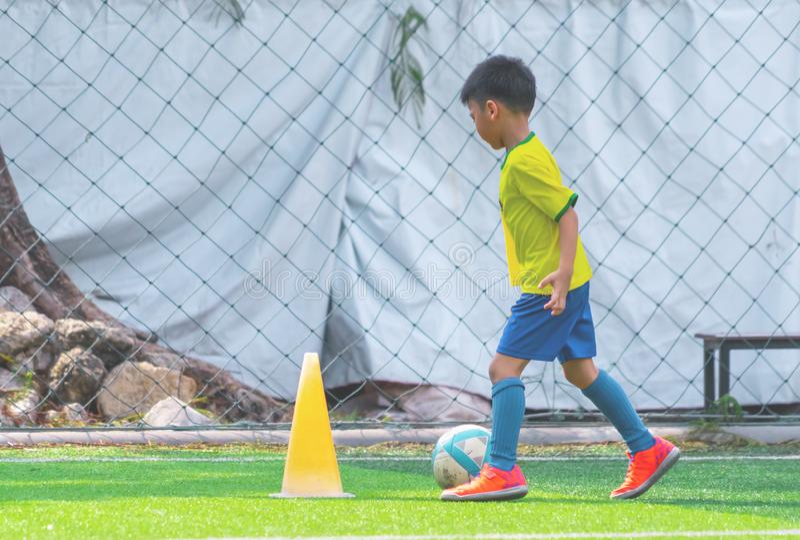 Children training and dibbling ball in soccer training stock photo