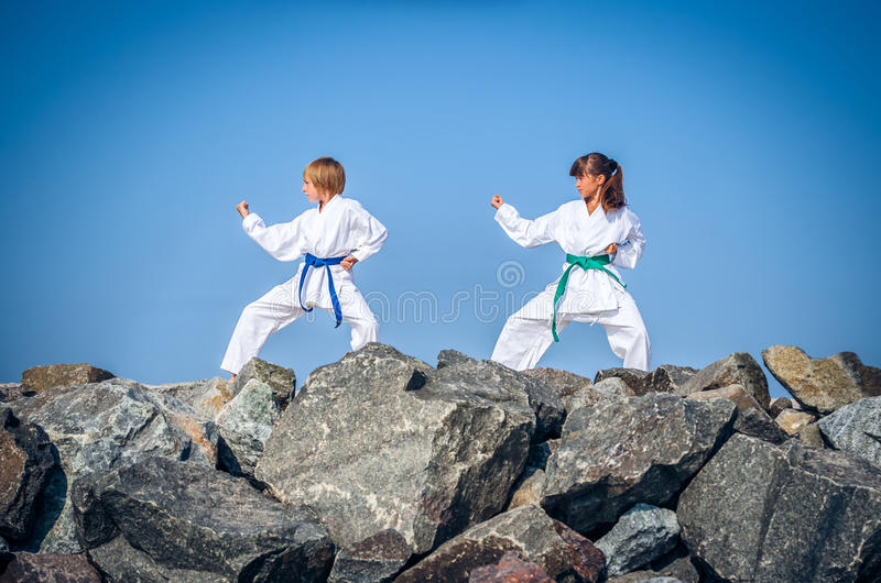 Children training karate on the stone coast royalty free stock photography