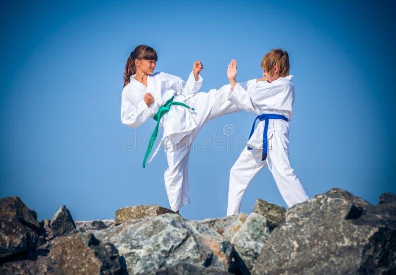 Children training karate on the stone coast royalty free stock photo