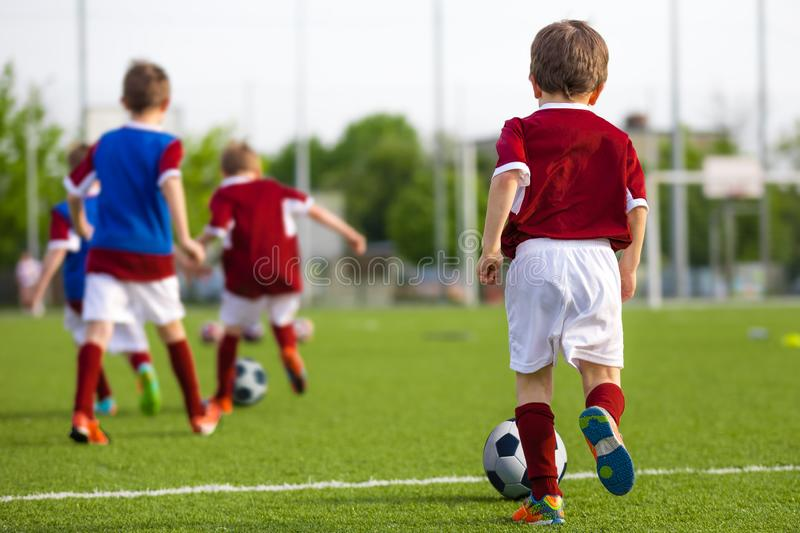 Children Training Soccer on Field. Young Kids Boys kicking Soccer Football Balls on Grass Pitch. Kids in Sportswear Practice Soccer Skills royalty free stock images