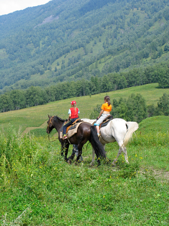 Children traveling in Altay mountains. Young girls traveling in Altay mountains on horses royalty free stock photo