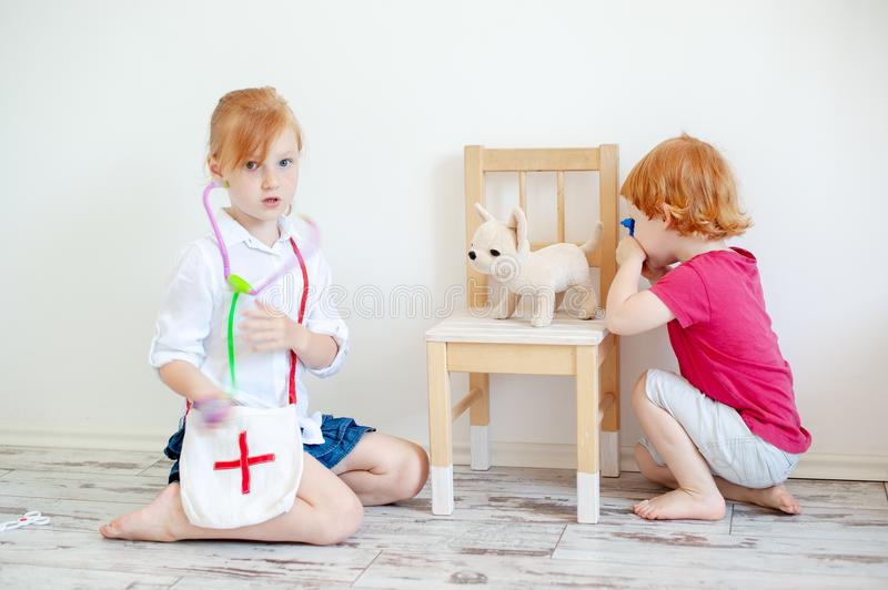 Children treat a toy dog, play a vet stock photo