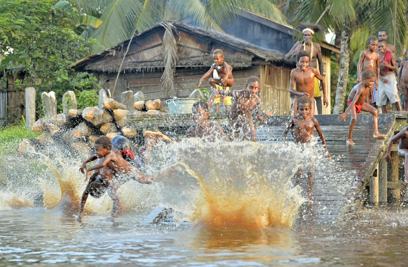 Children of the tribe of Asmat people bathe and swim in the river stock photos