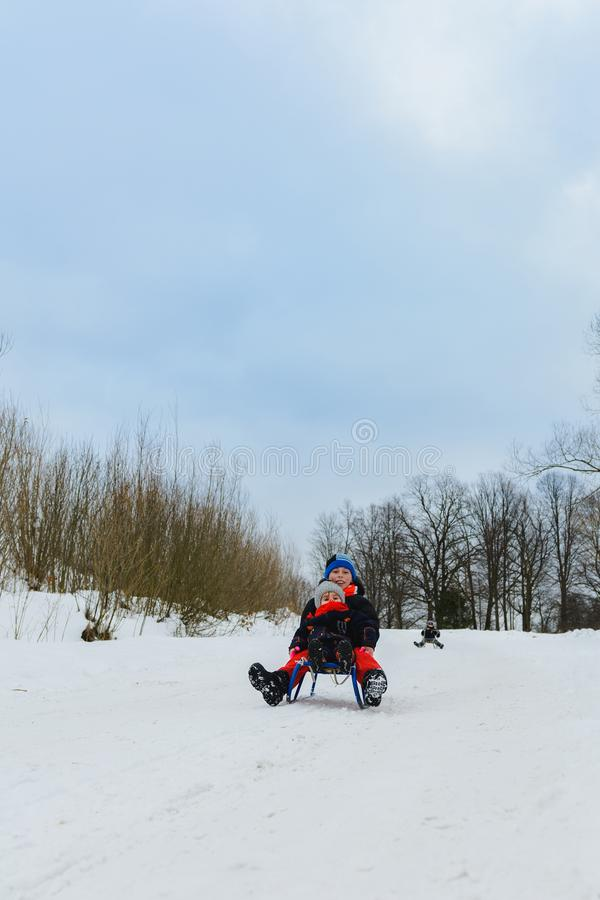 Children on two sledges descend from the hills stock photo