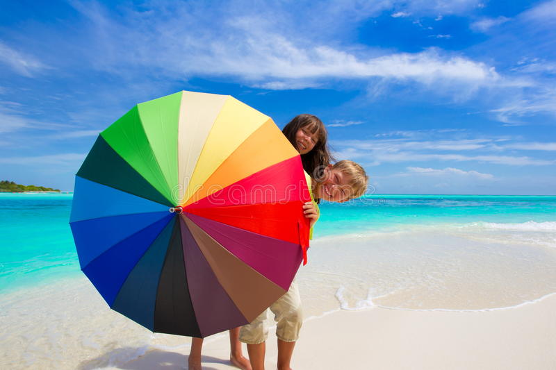 Children with Umbrella. Two children hiding behind a colorful umbrella on the beach