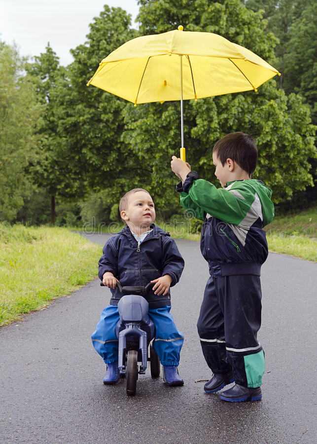 Children with umbrella. Children friends with yellow umbrella and toy bike in the rain stock photography
