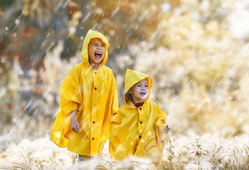 Children under the autumn rain royalty free stock photography