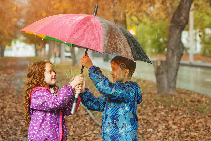 Children under umbrella enjoy to autumn rain royalty free stock image