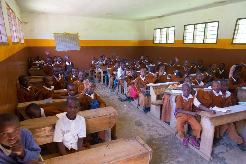 Children in uniforms in primary school classroom listetning to teacher in rural area near Arusha, Tanzania, Africa. Arusha, Tanzania- Jan 26, 2015: Children in royalty free stock photography