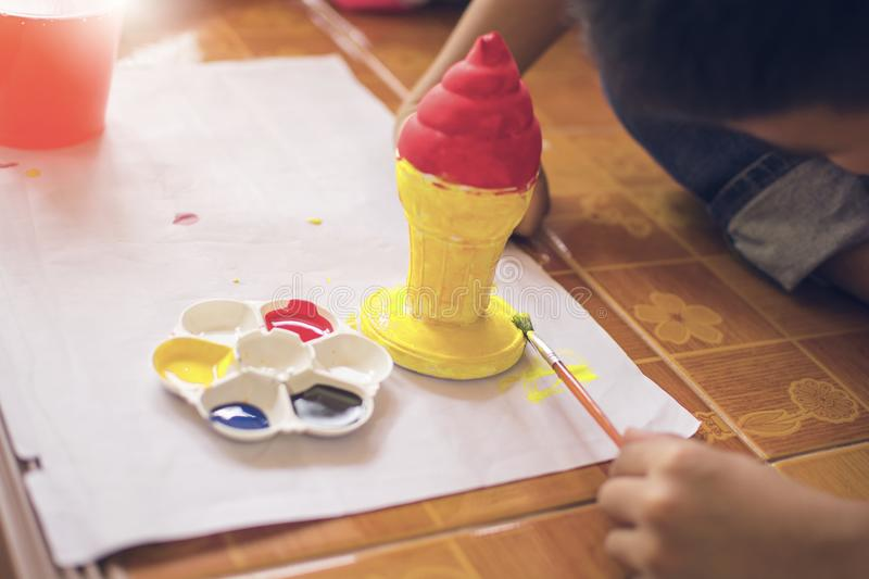 Children use brush to painting plastic ice cream cone with painting plate and bottle of water. Art learning royalty free stock images