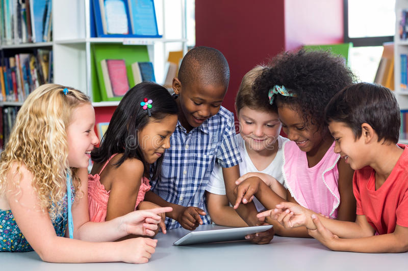 Children using digital table in library. Happy multi ethnic children using digital table in library royalty free stock photo