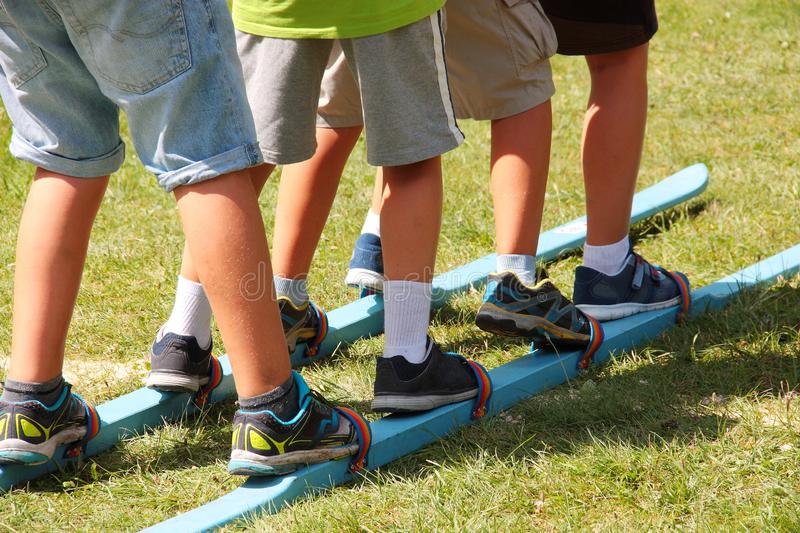 Children using together a pair of ski during summer games royalty free stock image