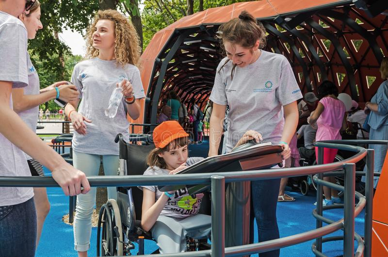Children and volunteers. Dnipro, Ukraine - June 27, 2018: Volunteers help children with special needs to have fun in an inclusive city park stock image