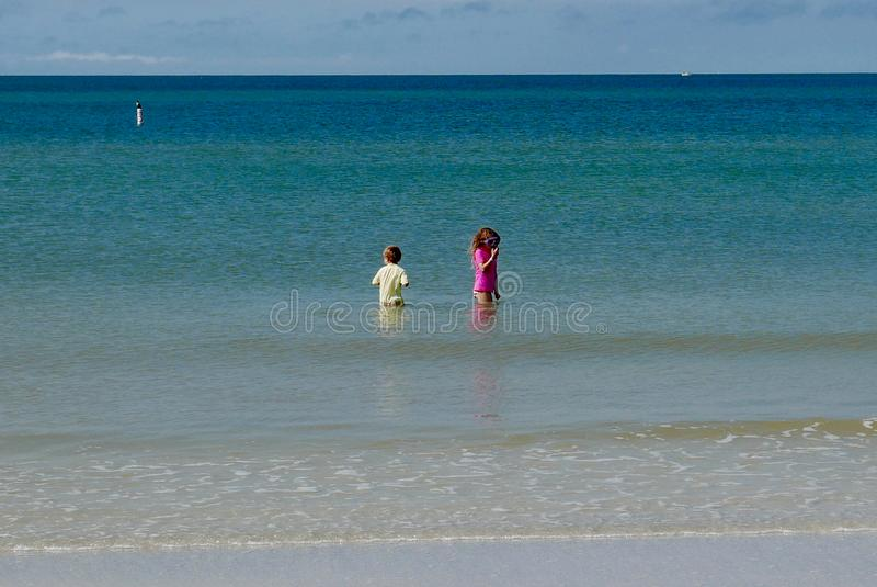 Children wading in the water in a turpuoise blue ocean stock photo