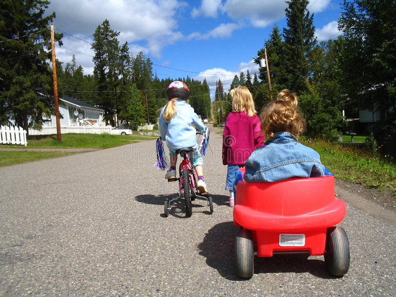 Children with wagon and bike royalty free stock photos