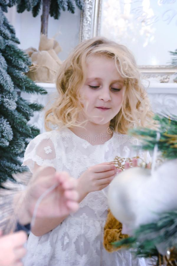 Children Waiting for the New Year and Christmas. Cute little girl decorating christmas tree by baubles at home. royalty free stock image
