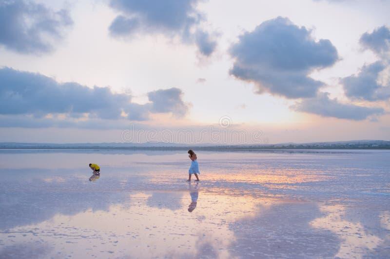 Children walk on Salty shore of the Laguna Salada de Torrevieja, Spain. stock image
