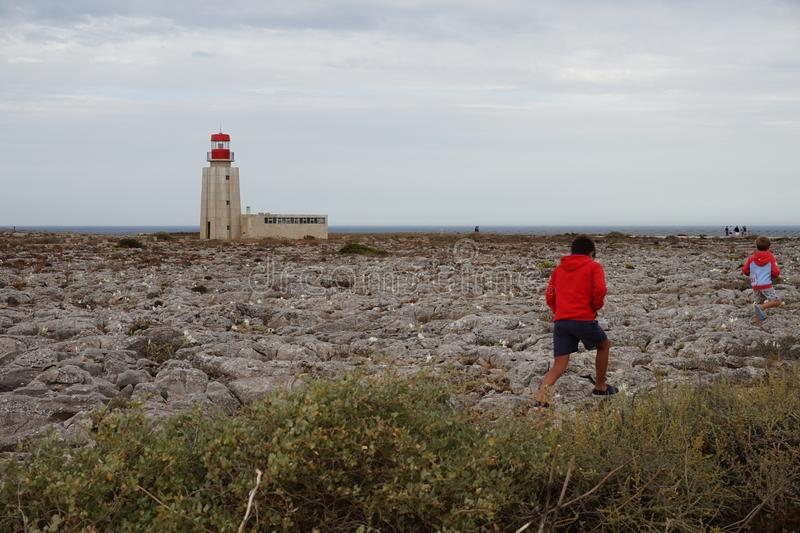 Children walking through the lighthouse in Portugal. Two children on their backs walk near a lighthouse. Landscape near the sea in Portugal stock image