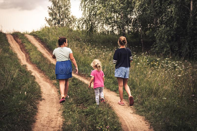 Children walking on rural road uphill towards dramatic sky on horizon in countryside  concept happy childhood lifestyle royalty free stock image
