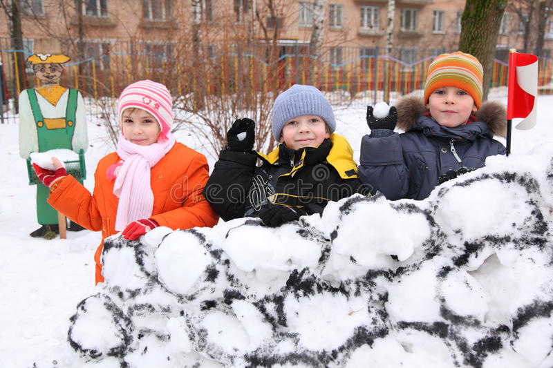 Children on wall of snow fortress in court yard. Three children on wall of snow fortress in court yard throw snowballs royalty free stock photo