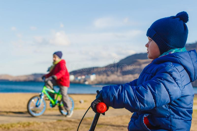 Children in warm jackets and hats ride bicycles in the spring outdoors on the background of the lake. And mountains royalty free stock photo