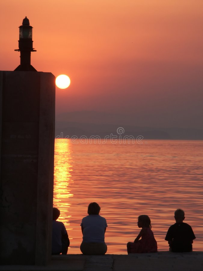 Children watch sunset stock images