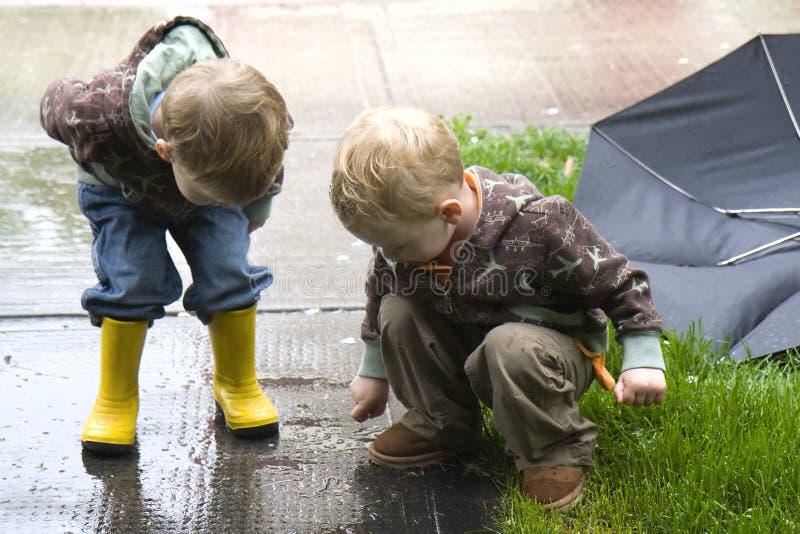 Children watch worm. Two three year old children watch worm crawling on sidewalk royalty free stock photo