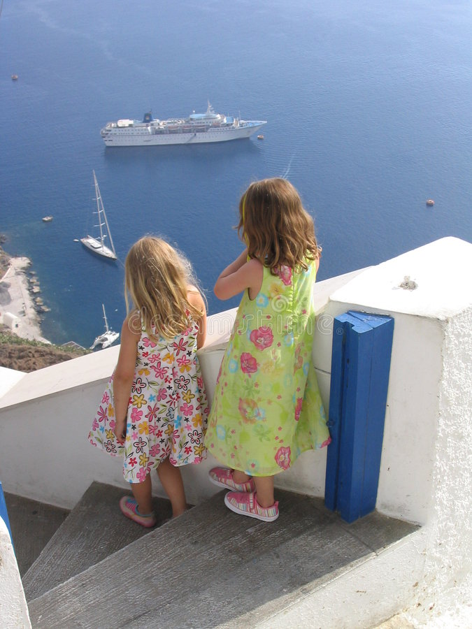 Children watching boats at Oia, Santorini, Greece. Children watching boats at Oia. Santorini, Greece stock photos