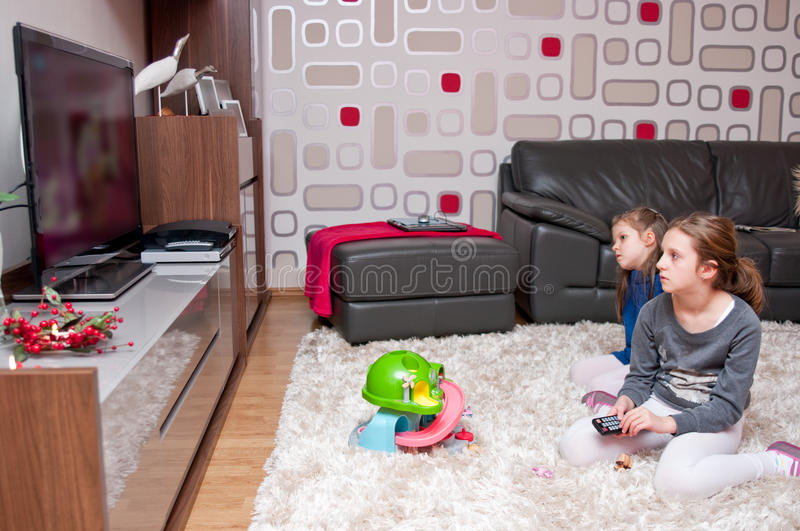 Children watching TV. In the modern living room royalty free stock image