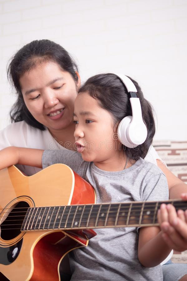 Children wear a white headphone. Mom is teaching her daughter to play guitar. Asian little girl learning to play music and sing a song. Children wear a white stock photo