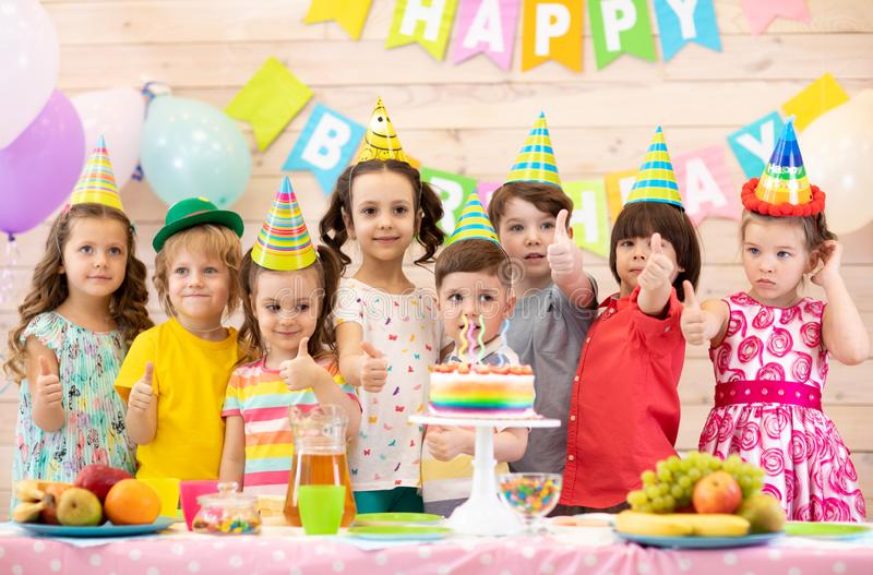 Children celebrating birthday party. Kids stand at festive table and show thumbs up stock photo