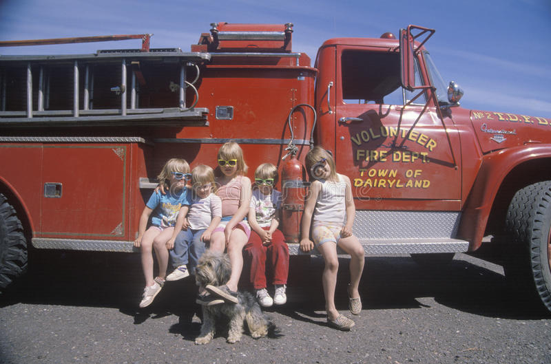Children wearing sunglasses with a fire truck, stock photos