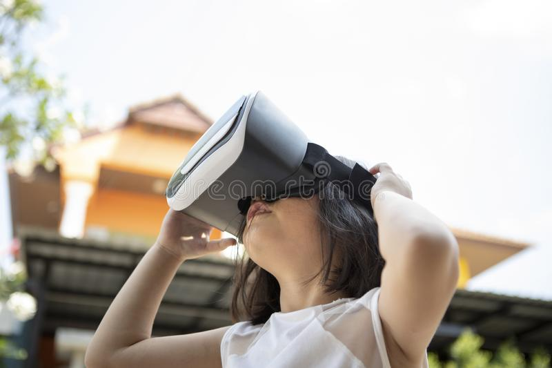Children wearing virtual reality glasses with fun and surprising face standing outdoor stock photos