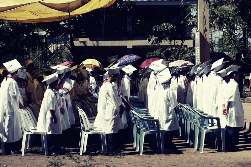 Children Wearing White Academic Gown during Graduation Ceremony at Daytime stock photos