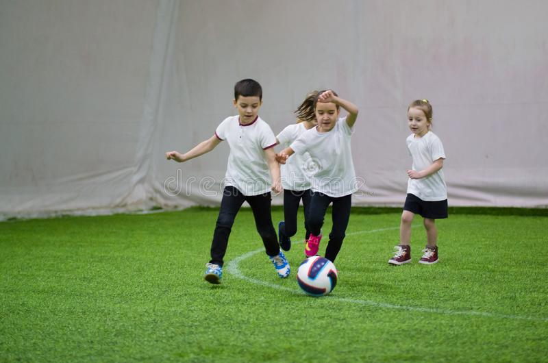 Children in white t-shirts playing football indoors. Kids running on the field after the ball stock images