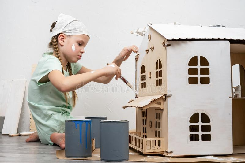 Children at work: The girl neatly paints the facade of the doll house with a small tassel in white. Authentic shot stock photography