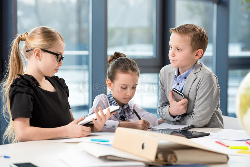 Children working in office. Like adult business people stock image