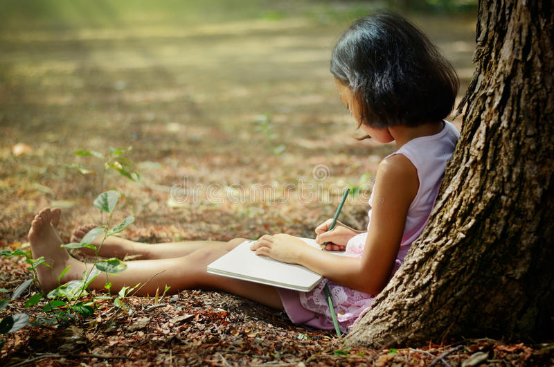 Children writing a book under a tree stock photo