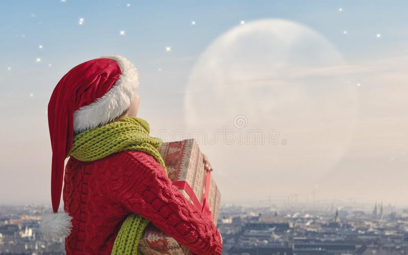 Children with xmas present. Merry Christmas! Cute little child with xmas present. Happy kid enjoy the holiday. Portrait of girl with gifts on cityscape stock images