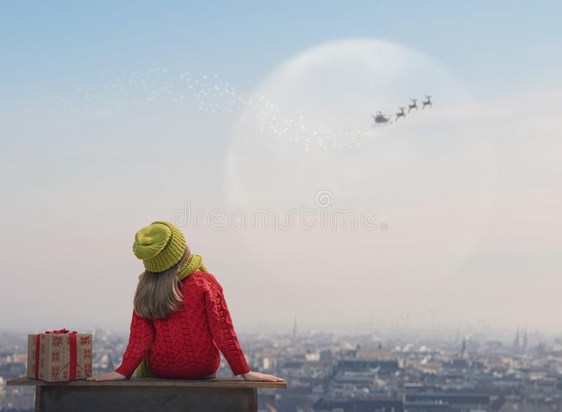 Children with xmas present. Merry Christmas! Cute little child with xmas present. Happy kid enjoy the holiday. Portrait of girl with gifts on cityscape stock photo