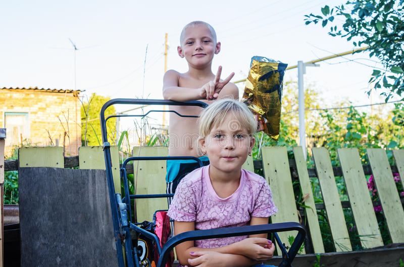 Download Children In The Yard Of The Rural House, Brother Sister Does Horns Stock Photo - Image: 83711249