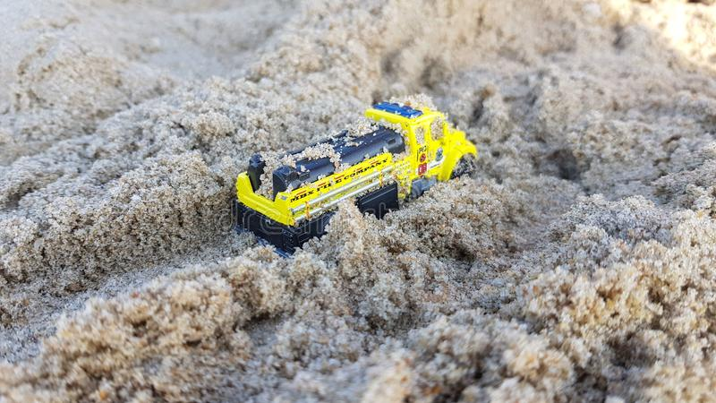 Children yellow car toy model in sand royalty free stock images