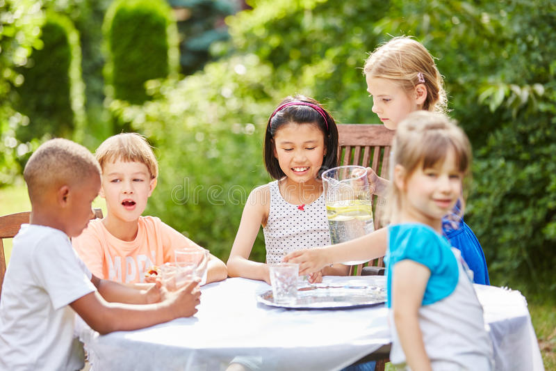 Childrens birthday party with kids drinking water. In summer royalty free stock images