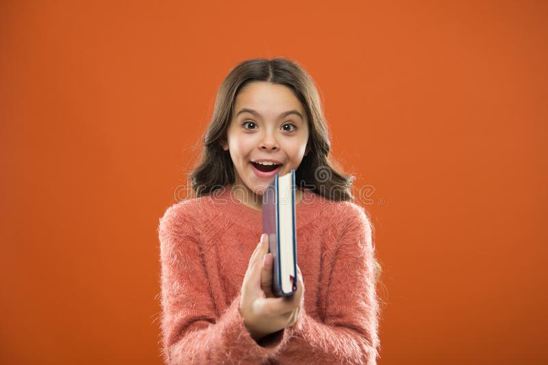 Childrens literature. Girl hold book read story over orange background. Child enjoy reading book. Book store concept. Wonderful free childrens books available royalty free stock photo