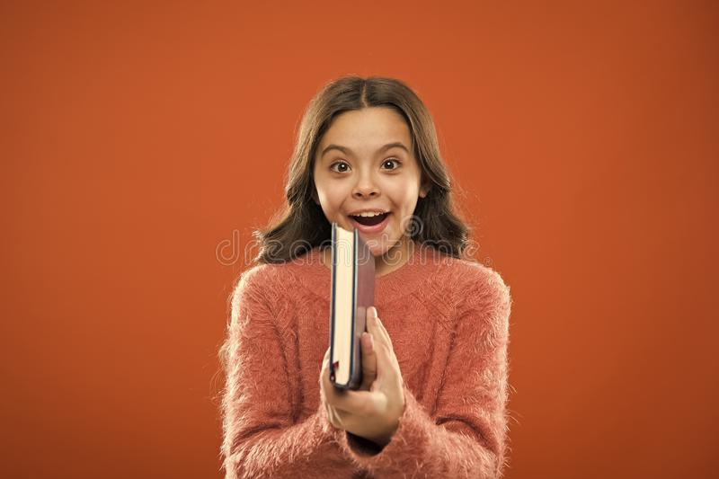 Childrens literature. Girl hold book read story over orange background. Child enjoy reading book. Book store concept. Wonderful free childrens books available royalty free stock image
