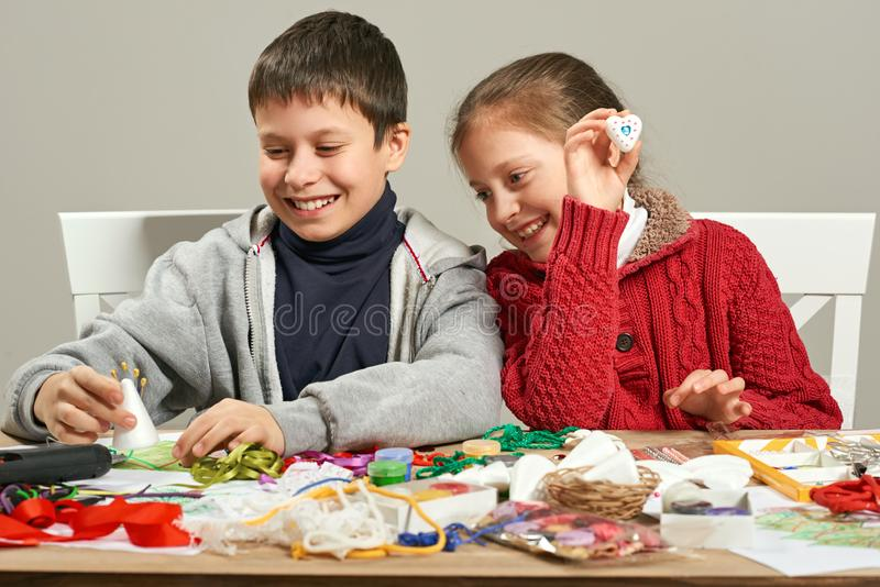 Childrens making decorations for new year holiday. Painting watercolors. Top view. Artwork workplace with creative accessories. stock images