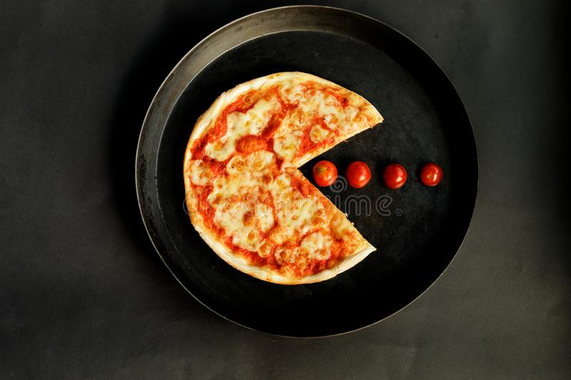 Chicken Margarita Pizza Shaped Like Pac-Man. A chicken margarita pizza in the shape of Pac-Man gobbling tomatoes, in a black pan royalty free stock photography