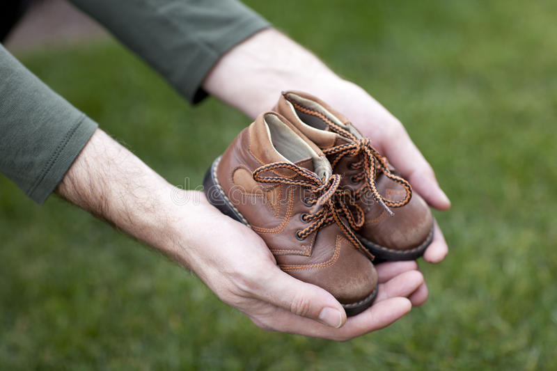 Childrens shoes. Dirty hands holding a pair of old childrens shoes royalty free stock images